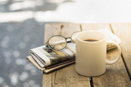 Läsglasögon på tidning och kaffemugg